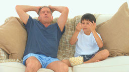 A man with his grandson watching a match on the tv Footage