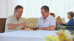 Men playing chess while their wives are speaking Footage