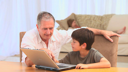 A grandfather and his grandson using a laptop Footage