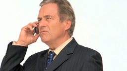 Aged businessman in suit taking a phone call Footage