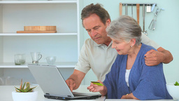Mature couple using a credit card Stock Video Footage