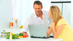 Lovely couple looking at a recipe on internet Footage