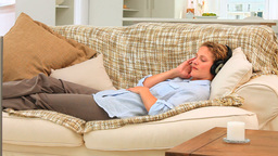 Woman lying and listening to music Footage