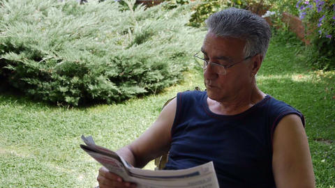 Old retired man reading newspaper Footage