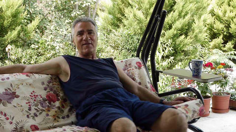 Old retired man on porch swing - Leisure Footage