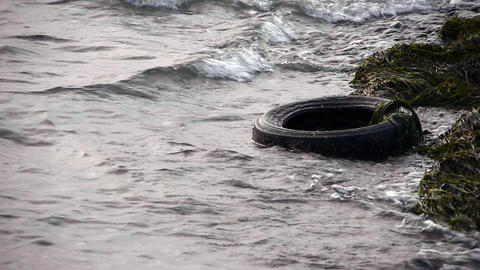 Old tyre in dirty polluted sea - Environment - Pollution Stock Video Footage