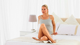 Blonde woman sitting on her bed Footage