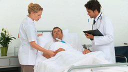 Doctors examining a sick man Stock Video Footage
