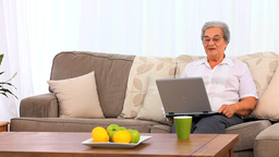 Mature woman laughing in front of her laptop Footage