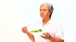 Mature woman eating salad Stock Video Footage