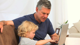 Boy with his grandfather looking at the laptop Footage