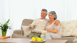 Mature couple eating popcorn in front of the tv Stock Video Footage