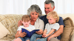 Grandparents reading a book to their grandchildren Stock Video Footage
