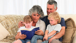 Grandparents reading a book to their grandchildren Footage