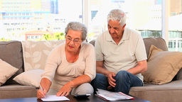 Mature couple calculating their domestics bills Stock Video Footage