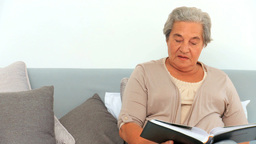 Mature woman looking at her photo album Live Action