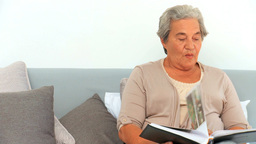 Mature woman looking at her photo album Stock Video Footage