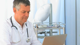 Serious doctor working on his laptop Stock Video Footage