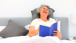 Elderely woman reading a book in her bed Footage