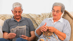 Woman knitting while her husband is reading the ne Footage