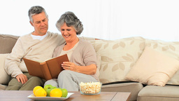 Mature couple looking at their album photo Footage