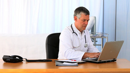 Busy doctor working on his laptop Stock Video Footage
