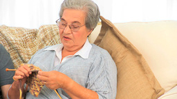 Woman knitting and talking with her husband Stock Video Footage