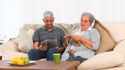 Senior woman knitting while her husband is reading Stock Video Footage