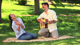 Attractive man playing guitar to his wife Footage