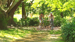Athletic young couple going cycling in a wood Footage