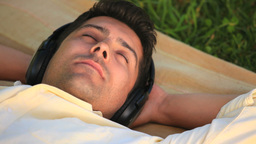 Man lying outdoors listening to music Stock Video Footage