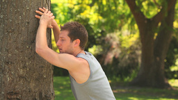 Athletic man leaning against a tree Footage