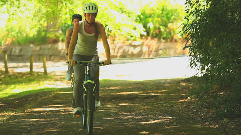 Sporting couple cycling on a path Footage