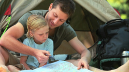 Father teaching his son to use a map Footage