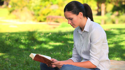 Woman sitting reading outdoors Footage