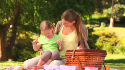 Mother with her daughter eating watermelon Footage