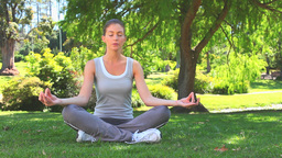 Attractive woman doing yoga on the grass Stock Video Footage