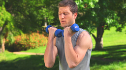 Brownhaired man using dumbbells Footage