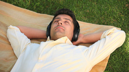 Man relaxing listening to music outdoors Footage