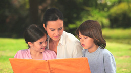 Mother outdoors with her children looking at a boo Stock Video Footage