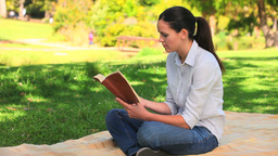 Attractive woman reading outdoors Footage