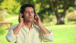 Smiling man listening to music outdoors Footage