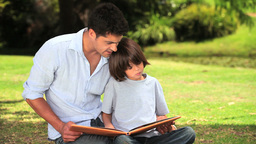 Father and son sitting reading outdoors Footage