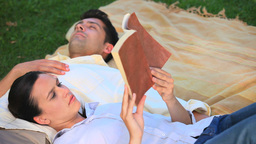 Man sleeping while his girlfriend is reading outdo Stock Video Footage
