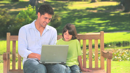 Father and son with laptop outdoors Stock Video Footage