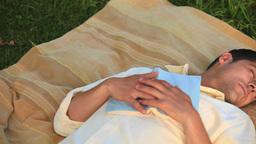Man asleep on a rug outdoors Footage