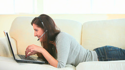 Young woman using headset and laptop Footage