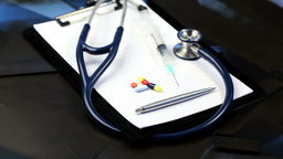 Stethoscope, syringe, pills and pen turning Footage