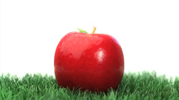 Red apple rotating on grass Stock Video Footage