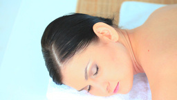 Darkhaired woman relaxing while having a massage Stock Video Footage
